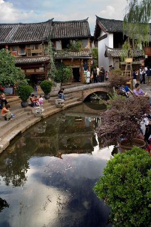 yunnan: Old Town Lijaing Yunnan Province China.  Lijiang is a city of canals and this is the center of the city with a reflection in the Canal