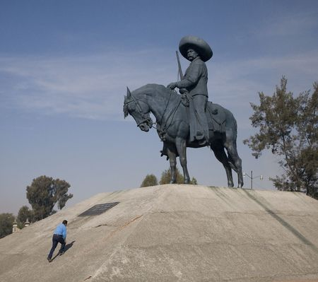 relative: Huge Statue of Emiliano Zapata, revolutionary hero, on horse Toluca Mexico.  Man climbing up statue shows relative size