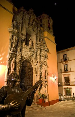 San Diego Church Guanajuato Mexico Night.  The statue celebrates the tradition in Guanajuato of meeting at this spot and singing through the streets. photo
