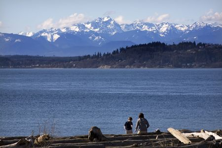 edmonds: Mother and Son in the distance at the Beach, Edmonds, Snohomish County, Washington with Olympic Mountains in Backgroundfocus. Stock Photo