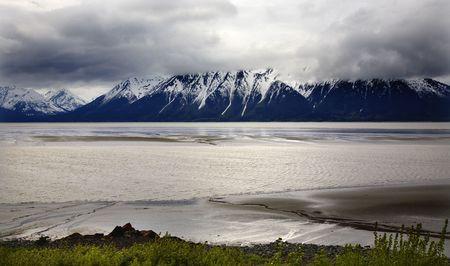 anchorage: Snow Mountain Ocean Seward Highway Anchorage Alaska Overcast Skies Green Grass Low Tide  Stock Photo