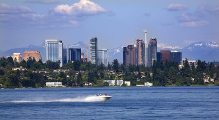 sharpen: City of Bellevue from Lake Washington with Speed Boat and Snow Capped Mountains in BackgroundrrResubmit--In response to comments from reviewer have further processed image to reduce noise, sharpen focus and adjust lighting. Stock Photo