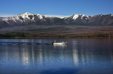 Lake McDonald Going Fishing Outboard in front of Snow MountainS Glacier National Park Montana photo