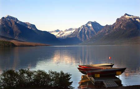 glacier national park: Lake McDonald Boats Snow Mountains at Glacier National Park Stock Photo