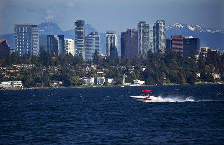 City of Bellevue from Lake Washington with Speed Boat and Snow Capped Mountains in Background  Stock Photo