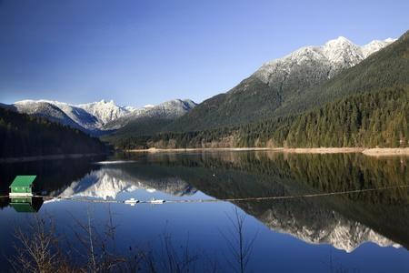 montañas nevadas: Capilano embalse Lago larga reflexión verde edificio presa Snowy dos leones montañas nevadas Vancouver Canadá noroeste Foto de archivo