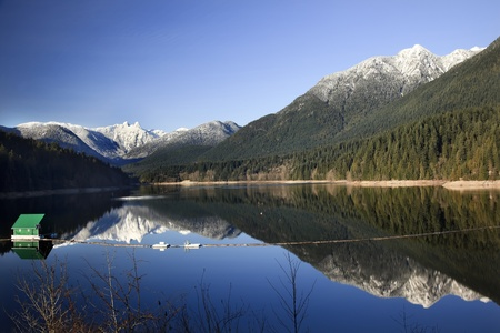 Capilano Reservoir Lake Long Reflection Green Building Dam Snowy Two Lions Snow Mountains Vancouver British Columbia Pacific Northwest Stock Photo