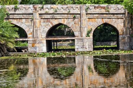 natural arch:  Athpula Eight Piers Stone Bridge Reflection Lodi Gardens New Delhi India 17th Century Bridge Stock Photo