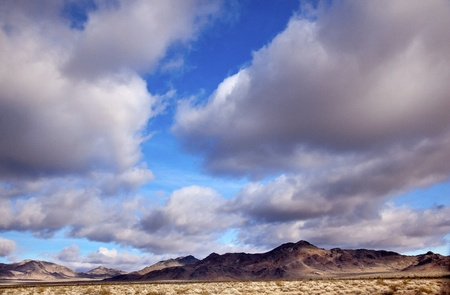 near death: Desert Cloudscape Blue Skies Clouds Towering Over Landscape California Near Death Valley Stock Photo