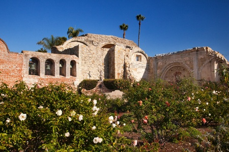 Mission San Juan Capistrano Church Rose Gardens and Ruins in California.  The statue of Father Junipero Serra, who founded the Mission in 1775, and mission bells in the back.  The church was destroyed in 1812 by earthquake. photo