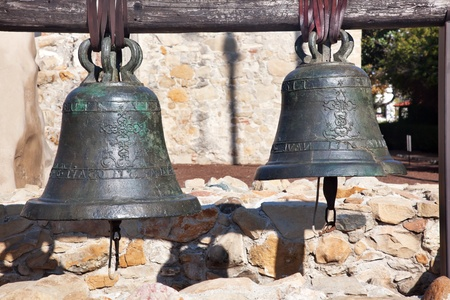 church bell: Old Brass Bells Mission San Juan Capistrano Churchand Ruins in California.  The church was destroyed in 1812 by earthquake and these are the old bells recovered from the ruins.