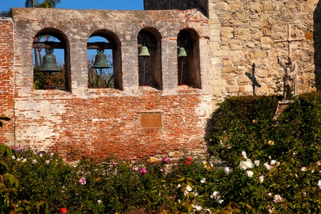 Mission San Juan Capistrano Church Rose Garden, Wall, Bells and Ruins in California.  The statue of Father Junipero Serra, who founded the Mission in 1775, and mission bells in the back.  The church was destroyed in 1812 by earthquake. photo