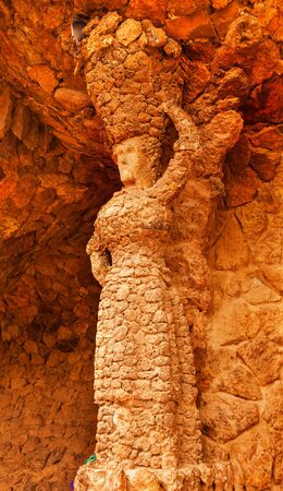 footway: Stone Woman Colonnaded Footway Under Viaduct designed by Antoni Gaudi Guell Park, Barcelona, Catalonia, Spain   Antonio Gaudi designed the wall with local stone, but the Stone Woman is rumored to have been created by one of Gaudi