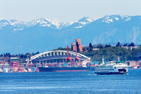 Seattle Washington Port Ferry with Cranes Containers and Freighters Ships at Pier to Be Unloaded and Stadium Cascade Mountains photo