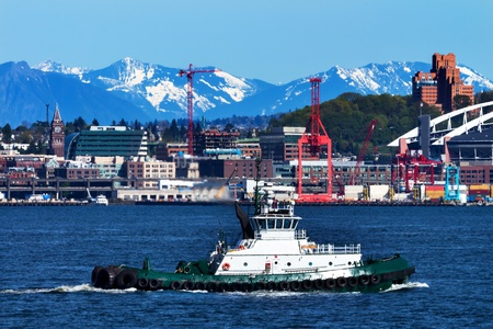Tug Boat Seattle Port with Red Cranes and Cascade Mountains in the Background  photo
