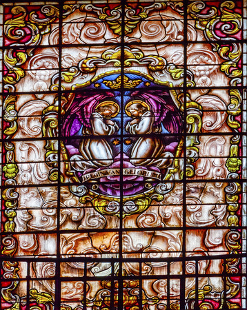 isidro: Stained Glass Angels Praying Basilica Santa Iglesia Collegiata de San Isidro Madrid Spain. Named after Patron Saint of Madrid, Saint Isidore, Church was created in 1651 Editorial