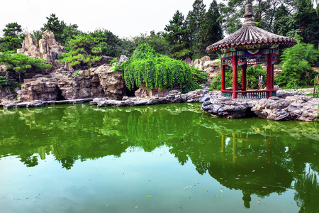 city park pavilion: Red Pavilion Rock Garden Water Pond Reflection Temple of Sun City Park, Beijing, China Willow Green Trees
