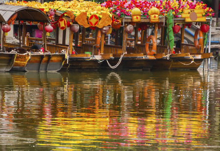 Flower Boats Reflection Lychee Bay Luwan Guangzhou Guangdong Province China.  Lychee Bay was founded in 209 in the Han Dynasty.  Canals have become a famous Guangzhou city park. photo