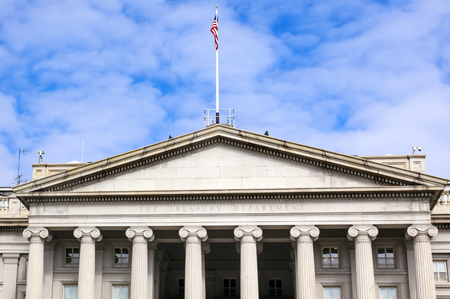US Treasury Department Front Columns and Flag Pennsylvania Ave Washington DC.  The Treasury is located next to the White House because President Andrew Jackson told his advisors that he wanted the National Bank to be right there where he could see it. Editorial