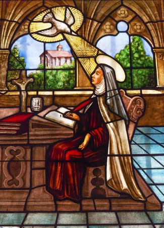 Saint Teresa Writing Stained Glass Convento de Santa Teresa Basilica Avila Castile Spain.  Convent founded in 1636 for Saint Teresa, Catholic nun, Counterreformation author, and Spanish mystic, who founded the Carmelite order. Died in 1582 and made a sain