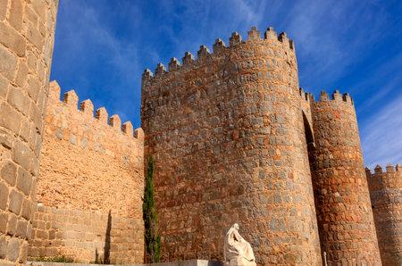 White Saint Teresa Statue Castle Walls Swallows Avila Castile Spain.  Avila described as the most 16th century town in Spain.  Saint Teresa Statue created 1972 by Juan Luis Vassallo Walls created in 1088 after Christians conquer  Moors