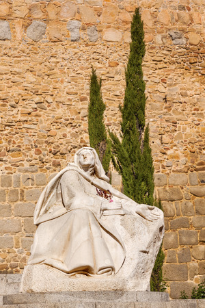 White Saint Teresa Statue Walls Castle Avila Castile Spain.  Avila described as the most 16th century town in Spain.  Saint Teresa Statue created 1972 by Juan Luis Vassallo. Walls created in 1088 after Christians conquer  Moors Editorial