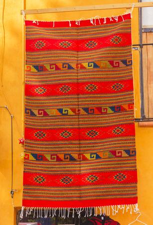 adobe wall: Colorful Souvenir Orange Mexican Blanket Yellow Adobe Wall San Miguel de Allende Mexico Stock Photo