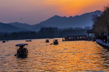 boas: Boats Reflection Sunset Orange Relfection West Lake Hangzhou Reflection Zhejiang China . Stock Photo