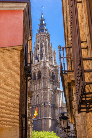 spanish flag: Cathedral Spire Tower Spanish Flag Narrow Streets Medieval City Toledo Spain.  Cathedral started in 1226 finished 1493 Stock Photo