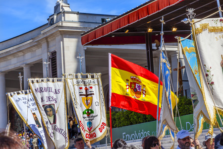 believers: Believers Banners Spanish Flag May 13 Apparation Day Basilica of Lady of Rosary Bell Tower Fatima Portugal. Church created on site where three Portuguese Shepherd children saw Virgin Mary of the Rosary.  May 13th day Virgin Mary appeared to the Peasants B