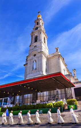 Priests May 13th Celebration of Marys Appearance Basilica of Lady of RosaryFatima Portugal. Church created on site where three Portuguese Shepherd children saw Virgin Mary of the Rosary.  Basilica created in 1953. Statement in back is about God and Love