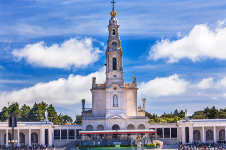 May 13th Celebration of Marys Appearance Basilica of Lady of Rosary Bell Tower Fatima Portugal. Church created on site where three Portuguese Shepherd children saw Virgin Mary of the Rosary.  Basilica created in 1953. Statement in back is about Invovled