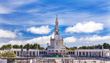 May 13th Celebration of Marys Appearance Basilica of Lady of Rosary Bell Tower Fatima Portugal. Church created on site where three Portuguese Shepherd children saw Virgin Mary of the Rosary.  Basilica created in 1953. Statement in back is about God and L Editorial