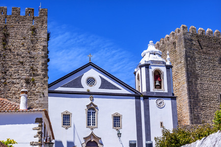 Sao Pedro Church Narrow White Street 11th Century Medieval Town Obidos Portugal. Church built in the late 13thearly 14th century. Castle and walls built in 11th century after town taken from the Moors. Stock Photo