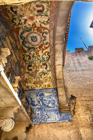 castle wall: Porta da Vila Southern Gate 18th Century Tiles 11th Century Castle Wall  Obidos Portugal. Castle and walls built in 11th century after town taken from the Moors.
