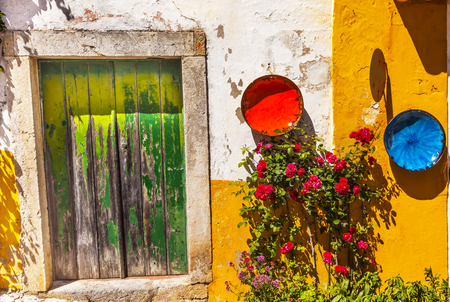 green door: White Yellow Wall Green Door Orange Blue Bowls Red Roses Street 11th Century Medieval Town Obidos Portugal.