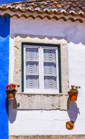 11th: White Blue Wall Flowers Street Lace Window 11th Century Medieval Town Obidos Portugal.