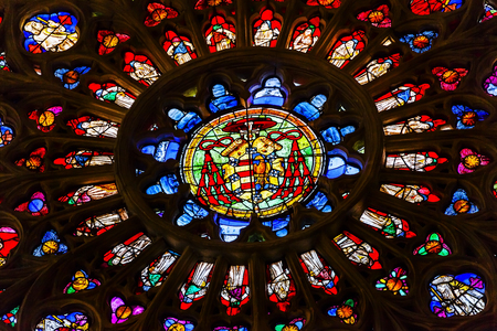 coat of arms: Rose Window Coat Arms Cardinal Hat Stained Glass Cathedral Spanish Flag Toledo Spain.  Cathedral started in 1226 finished 1493 Editorial