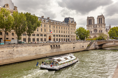 middle ages boat: Tour Boat Seine River Notre Dame Spires Towers Bridge Overcast Skies Notre Dame Cathedral Paris France.  Notre Dame was built between 1163 and 1250 AD.