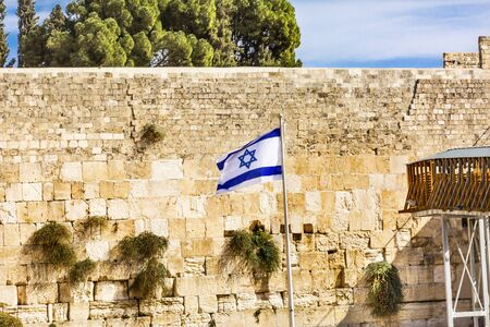 Israeli Flag WesternWailing Wall of Ancient Temple Jerusalem Israel.  Western wall of the Ancient Jewish Temple built in 100BC by Herod the Great on the Temple Mount.  Judaisims most holy site