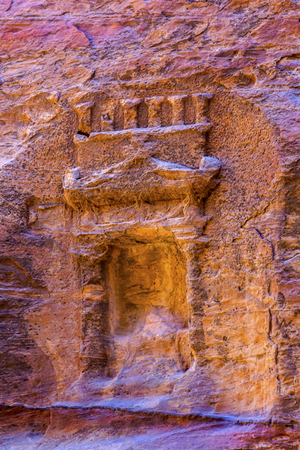 Small Rose Red Rock Tomb Outer Siq Canyon  Petra Jordan.  Built by the Nabataens in 200 BC to 400 AD.  Rose Red canyon walls create many abstracts close up.  Inside the Tombs, the rose red can become blood red.  Reds are created by magnesium in sandstone. Stock Photo