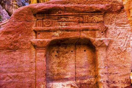 reds: Tomb Outer Siq Canyon Petra Jordan Petra Jordan.  Colorful Yellow Pink Canyon becomes rose red when sun goes.  The rose red can become blood red.  Reds are created by magnesium in sandstone. Stock Photo