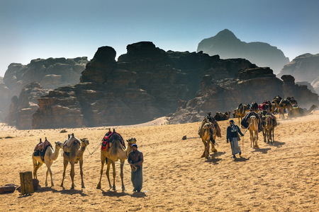 Arab Bedouin Guides Camels Rock Formations Yellow Sand Camel Wadi Rum Valley of the Moon Jordan.  Inhabited by humans since prehistoric times, place where TE Lawrence of Arabia in the early 1900s