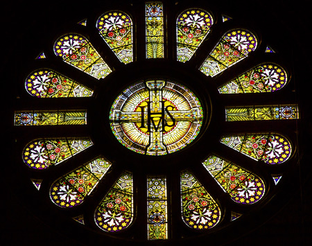 IHS Rose Window Stained Glass Saint Nicholas Church Amsterdam Netherlands. Roman Catholic Church Cathedral built in 1883, called Saiint Nicholas Within the Walls.  IHS is a Christogram for Jesus.  IHS comes from the Greek Letters I and H, which are the fi Editorial