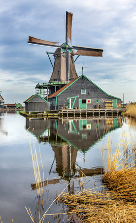 zaan: Wooden Windmill Zaanse Schans Old Windmill Village Countryside Holland Netherlands. Working windmills from the 16th to 18th century on the River Zaan.  Windmills powered industries in Holland, such as ship builidng, vegetable oil production. Stock Photo