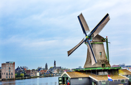 water turbine: Wooden Lumber Windmill Zaanse Schans Old Windmill Village Countryside Holland Netherlands. Working windmills from the 16th to 18th century on the River Zaan.  Windmills powered industries in Holland, such as ship builidng, vegetable oil production. Stock Photo