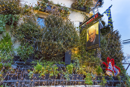 The Churchill Arms Pub Restaurant Kensington London England.  Famous pub and restaurant in London.  Stared as a pub in 1750.  Became Churchill Arms in World War 2 because Churchills parents used to visit the pub. Editorial
