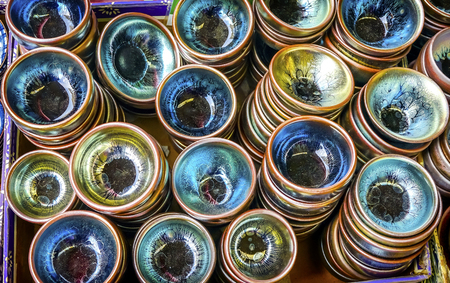 Old Chinese Ceramic Glass Plates  Panjuan Flea Market  Beijing China. Panjuan Flea Curio market has many fakes, replicas and copies of older Chinese products, many ancient.