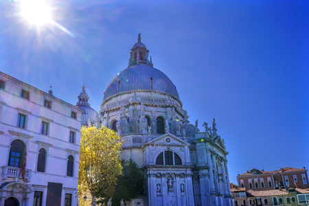 Sun Sunflare Santa Maria della Salute Church Basilica Dome Venice Italy. Competed in 1681 dedicated to our Lady of Health because of the 1630 outbreak of plague, which wiped out 13 of Venice population.   Banco de Imagens