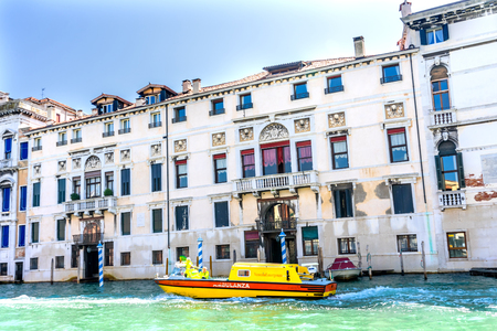 Yellow Ambulance Colorful Grand Canal Venice Italy.  The three Italian words on the ambulance say ambulance and Venice Emergency.